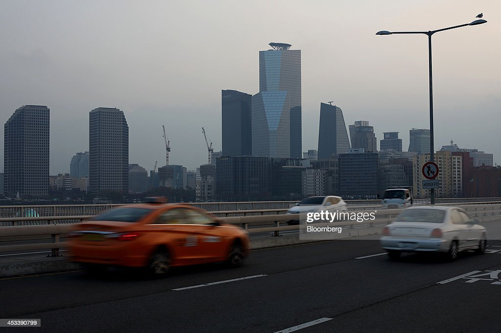 Traffic moves along a bridge over the Han River as commercial buildings stand in the Yeouido financial district in Seoul, South Korea, on Tuesday, Dec. 3, 2013. South Korea's economy will grow 3.9 percent next year - the fastest pace since 2010 - after a 2.8 percent expansion in 2013, the finance ministry projected in September. Photographer: SeongJoon Cho/Bloomberg via Getty Images