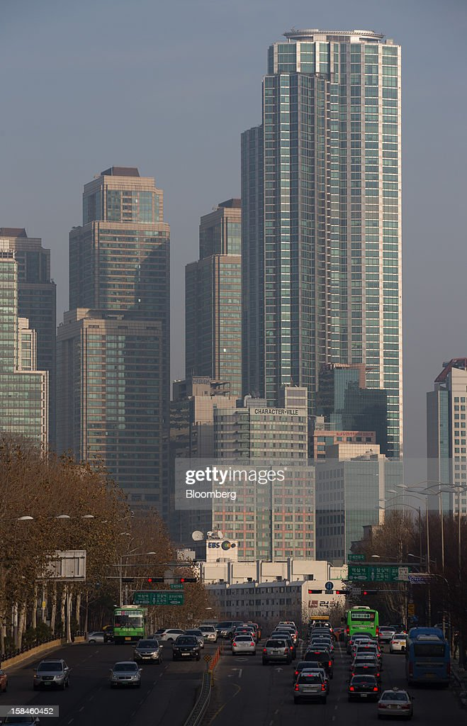 Traffic moves along a road in front of high rise residential buildings in the Gangnam district of Seoul, South Korea, on Sunday, Dec. 16, 2012. South Koreans vote on Dec. 19 to replace President Lee Myung Bak, whose five-year term ends in February. Photographer: SeongJoon Cho/Bloomberg via Getty Images