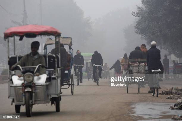 Traffic moves along a road shrouded in haze in New Delhi India on Monday Jan 20 2014 India China and Brazil three of the largest developing nations...