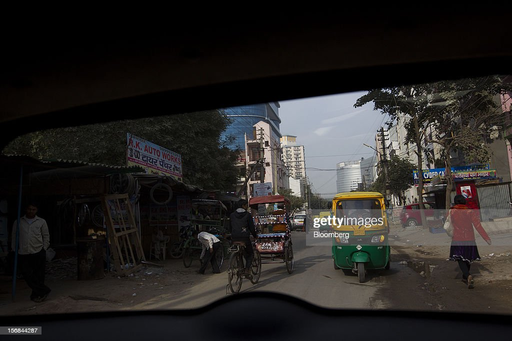 Traffic moves along a street in Gurgaon, India, on Wednesday, Nov. 21, 2012. Indian Prime Minister Manmohan Singh aims to spur spending on infrastructure to revive a faltering economy and tackle bottlenecks contributing to one of Asia's highest inflation rates. Photographer: Brent Lewin/Bloomberg via Getty Images