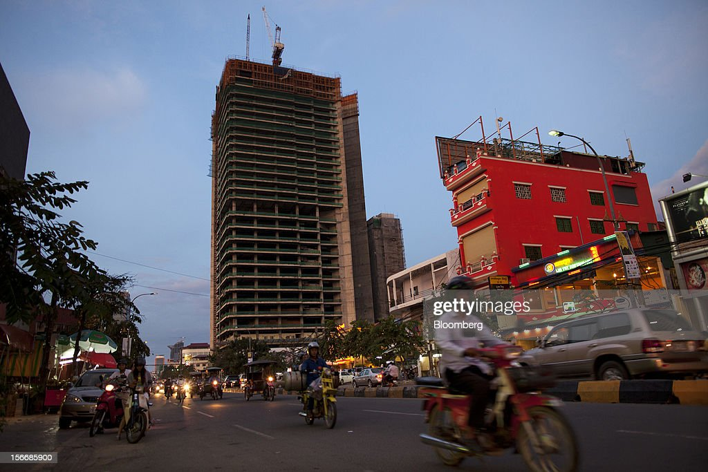 Traffic moves along the Monivong Boulevard past the Gold Tower 42 project, developed by Yon Woo Cambodia Co., center, as it stands unfinished in Phnom Penh, Cambodia, on Sunday, Nov. 18, 2012. U.S. President Barack Obama arrives in Phnom Penh later today to join the Association of Southeast Asian Nations (Asean) East Asia Summit, which also includes leaders from Japan, South Korea, India, Russia, Australia and New Zealand. Photographer: Will Baxter/Bloomberg via Getty Images