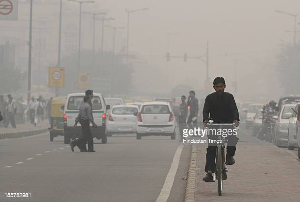 Traffic moves amid a blanket of smog caused by a mixture of pollution and fog at NCR region on November 7 2012 in New Delhi India