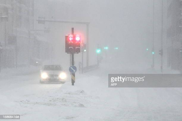 Traffic moves on snow covered roads in Kristiansand on December 23 after storms and heavy snow closed roads and made travel difficult in southern...