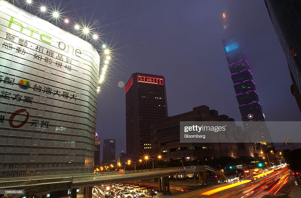 Traffic moves past a billboard advertisement for HTC Corp.'s One X+ smartphone, left, and the Taipei 101 building, right, in Taipei, Taiwan, on Sunday, Jan. 6, 2013. HTC is scheduled to release fourth-quarter earnings on Jan. 7. Photographer: Maurice Tsai/Bloomberg via Getty Images