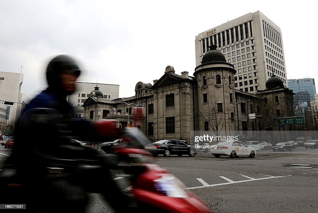 Traffic moves past the Bank of Korea headquarters in Seoul, South Korea, on Thursday, April 11, 2013. The Bank of Korea held borrowing costs unchanged for a sixth month, resisting pressure from the government for a reduction even as a sliding yen hurts the nation's exporters and North Korea threatens war. Photographer: SeongJoon Cho/Bloomberg via Getty Images