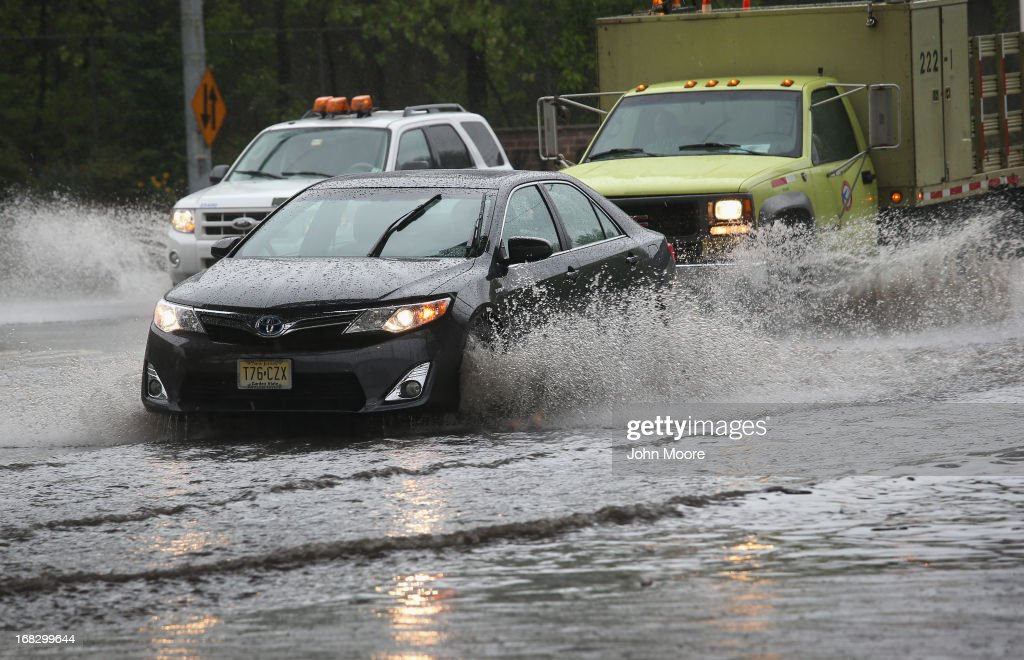 Traffic moves through floodwaters at an underpass on May 8, 2013 in Jersey City, New Jersey. Heavy rains flooded streets, stranding some motorists during morning rush hour traffic.
