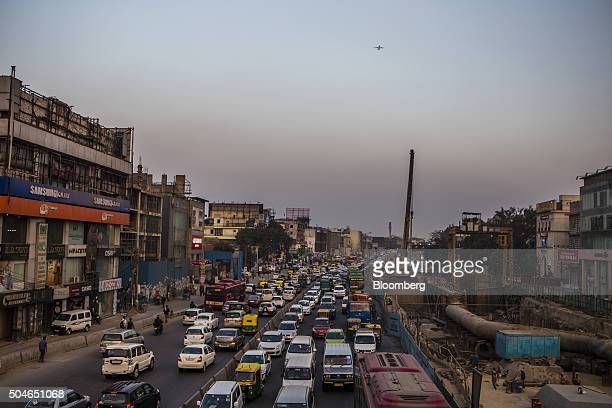 Traffic moving along a highway passes a Delhi Metro construction site right during evening rush hour in Delhi India on Monday Jan 11 2016 In a city...