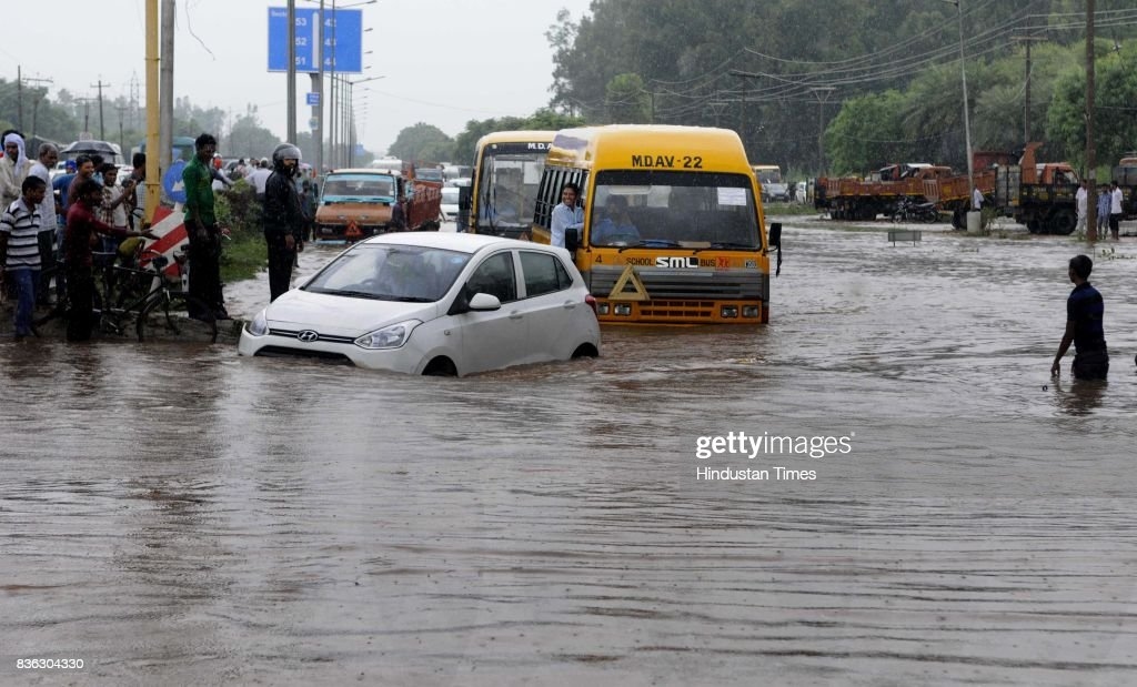 Traffic moving in waterlogged road at 45-50 light point due to rain on August 21 2017 in Chandigarh, India. Heavy rainfall on morning brought the tri-city (Chandigarh, Mohali, Panchkula) to a stand still as poor drainage system gave way to roads being flooded with water. The rainfall left the cars of commuters stuck in middle of the roads forcing them to leave their cars stranded.