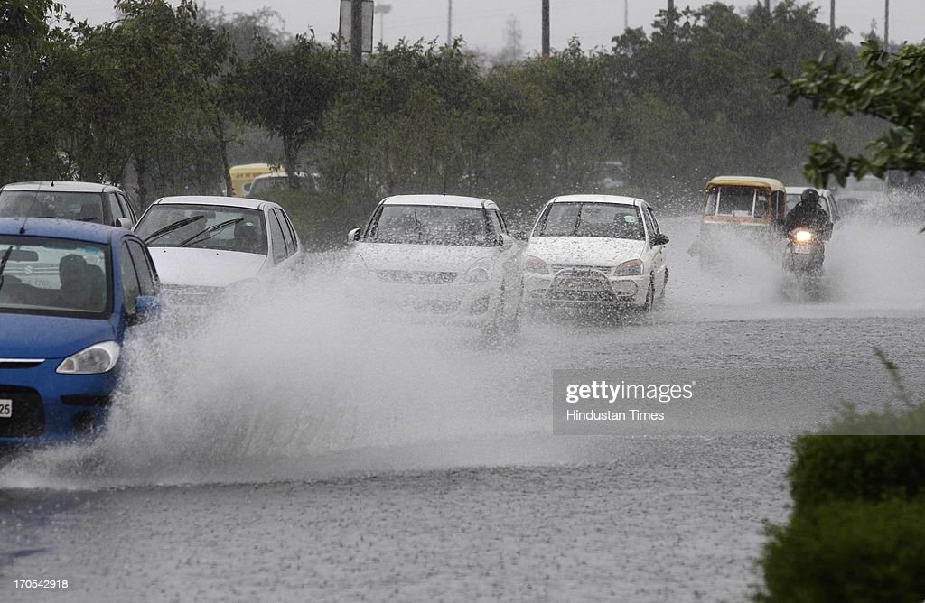 Traffic moving on water logged road during the heavy pre monsoon rain on June 14, 2013 in New Delhi, India. The city received 11.6 mm rainfall and the humidity oscillated between 47 and 91 percent.