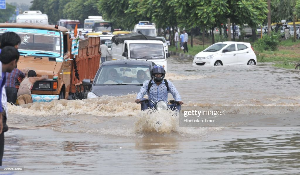 Traffic moving on waterlogged road of sector 44-50 dividing after the heavy rain on August 21, 2017 in Chandigarh, India. Heavy rainfall on morning brought the tri-city (Chandigarh, Mohali, Panchkula) to a stand still as poor drainage system gave way to roads being flooded with water. The rainfall left the cars of commuters stuck in middle of the roads forcing them to leave their cars stranded.
