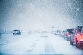 Winter weather and slow moving traffic creeping along a snow covered and icy freeway in a winter snow storm blizzard. Taillights are on in low light and low visibility road conditions. Copy space avai