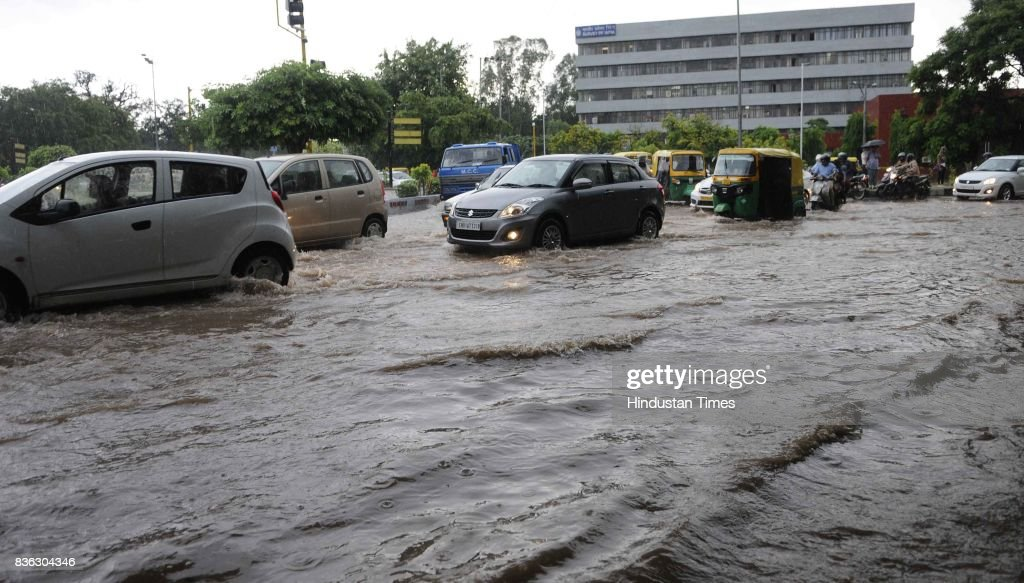 Traffic moving through waterlogged road at 32-33 light point due to rain on August 21, 2017 in Chandigarh, India. Heavy rainfall on morning brought the tri-city (Chandigarh, Mohali, Panchkula) to a stand still as poor drainage system gave way to roads being flooded with water. The rainfall left the cars of commuters stuck in middle of the roads forcing them to leave their cars stranded.