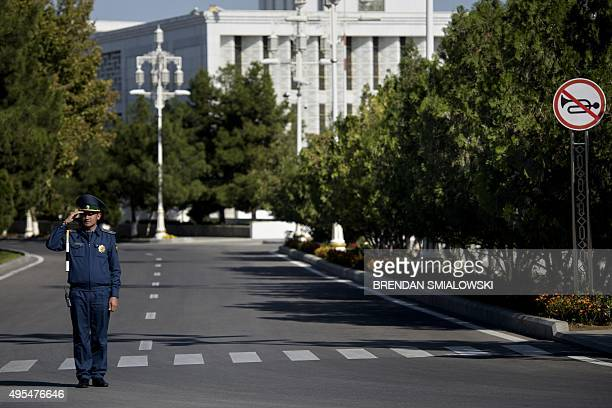 A traffic officer salutes while a motorcade ferrying US Secretary of State John Kerry drives past on November 3 2015 in Ashgabat Kerry is traveling...