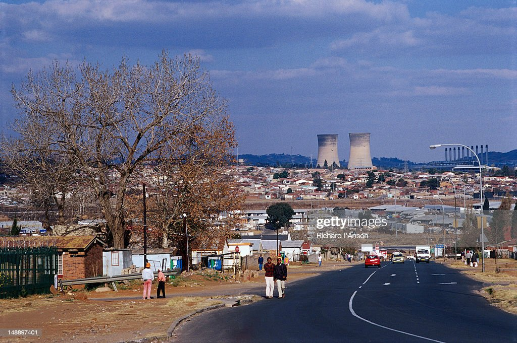 Traffic on a main road in the township, with power station chimneys in the distance.