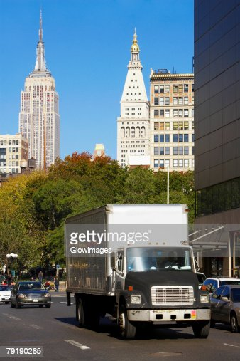 Traffic on a road with skyscrapers in the background, Empire State Building, Manhattan, New York City, New York State, USA : Stock Photo
