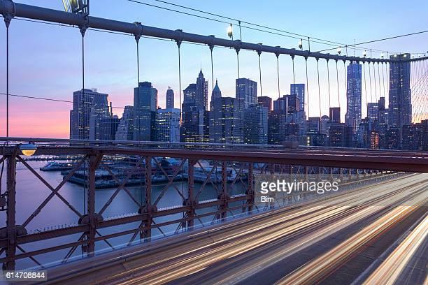 Verkehr auf der Brooklyn Brücke in der Abenddämmerung, Blick auf die Skyline von Manhattan, New York