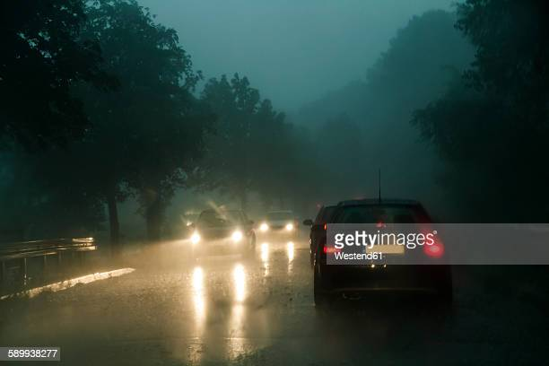 Traffic on county road at rainstorm by twilight