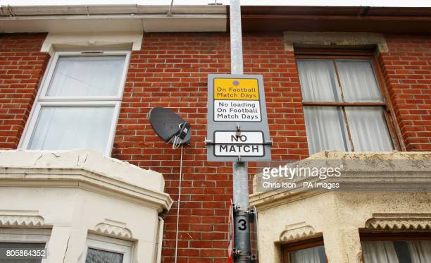 A traffic parking sign outside Fratton Park home of Portsmouth Football Club near a domestic satellite dish on a terraced property