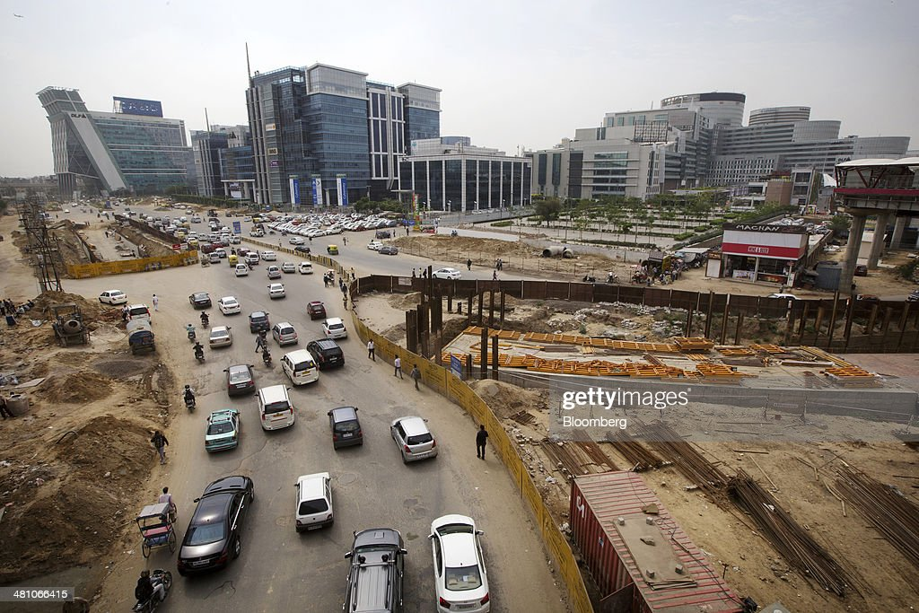 Traffic passes a construction site as DLF Cybercity, a 128 acre integrated business district, stands in the backgound in Gurgaon, India, on Wednesday, March 26, 2014. Indian stocks rose, sending the benchmark index to a record, after the rupee rose to an eight-month high and sovereign bonds gained on speculation the worlds largest democracy will elect a government capable of reviving economic growth. Photographer: Kuni Takahashi/Bloomberg via Getty Images