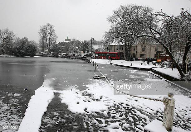 Traffic passes a half frozen Carshalton Ponds on January 13 2010 Carshalton England Further snow showers have caused the closure of Gatwick Airport...