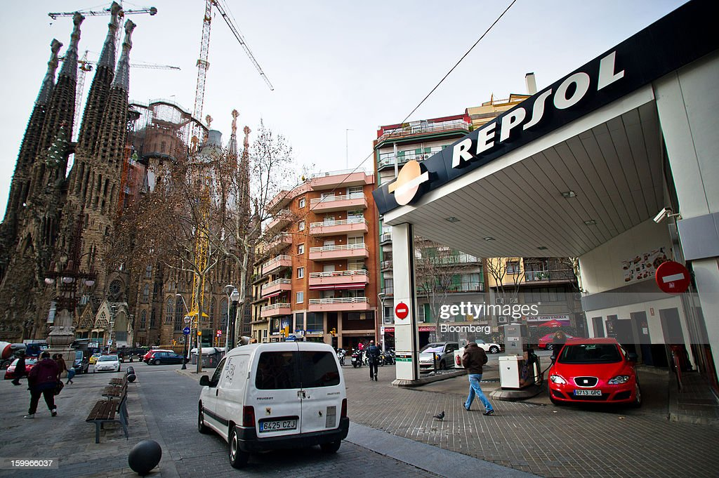 Traffic passes a Repsol SA gas station near the Sagrada Familia cathedral in Barcelona, Spain, on Wednesday, Jan. 23, 2013. Repsol SA, Spain's largest energy company, expects to sell liquefied natural gas assets for about 2 billion euros ($2.7 billion) by early February, according to a person familiar with the matter. Photographer: David Ramos/Bloomberg via Getty Images