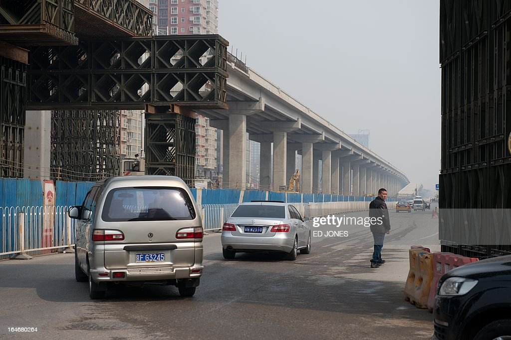 Traffic passes beneath a high-speed rail construction project in Beiing on March 26, 2013. Economic liberalisation has slowed in China, the Organisation for Economic Cooperation and Development (OECD) said in a major report on March 22, urging the country's Communist rulers to step up efforts to level the playing field for state-owned and private firms. AFP PHOTO / Ed Jones