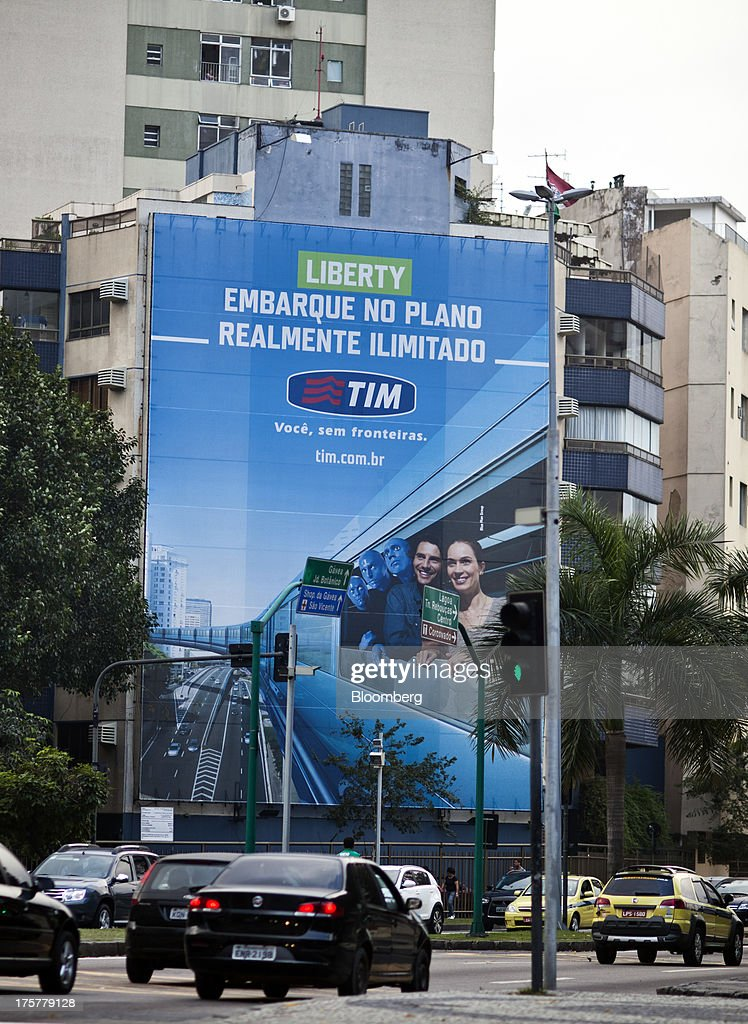 Traffic passes by a building with a large advertisement for Tim Participacoes SA in Rio de Janeiro, Brazil, on Tuesday, Aug. 6, 2013. Tim Participacoes SA, Brazils best-performing telecommunications stock this year, is gaining market share by undercutting rivals on voice and data plans. Photographer: Lianne Milton/Bloomberg via Getty Images