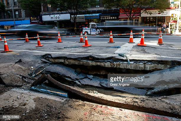 Traffic passes by a sinkhole caused by a water main break on Amsterdam Avenue in the Upper West Side section of Manhatten August 30 2016 in New York...