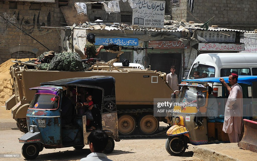Traffic passes by Pakistani soldiers in an armoured personnel carrier deployed near a voting station ahead of re-polling on National assembly seat NA250 in Karachi on May 18, 2013, where complaints of rigging and irregularities were reported in general election May 11. The army is set to be deployed at 43 polling stations of NA-250, PS-112 and PS-113 Karachi ahead of re-polling on May 19, a media report said. AFP PHOTO/Asif HASSAN
