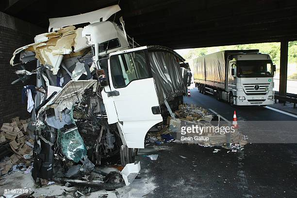 Traffic passes by the remains of a truck that crashed into another truck under a train bridge on the A10 highway near Michendorf on June 6 2008...