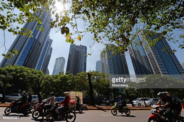 Traffic passes highrise buildings in the central business district of Jakarta Indonesia on Tuesday Dec 10 2013 Indonesia's central bank is scheduled...