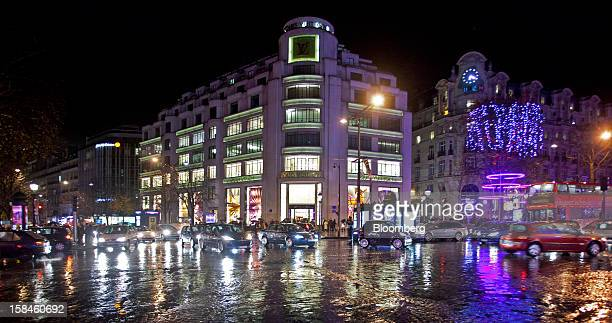 Traffic passes the illuminated Louis Vuitton store operated by LVMH Moet Hennessy Louis Vuitton SA on the ChampsElysees in Paris France on Saturday...