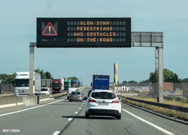 Traffic passes under a sign on a road on the outskirts of Calais on July 5 which reads 'slow down pedestrians and obstacles on the road' The signs...