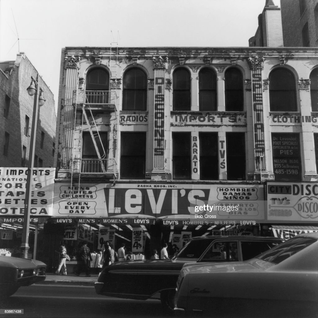 Traffic passing a clothing shop in downtown Los Angeles, California, 1975.