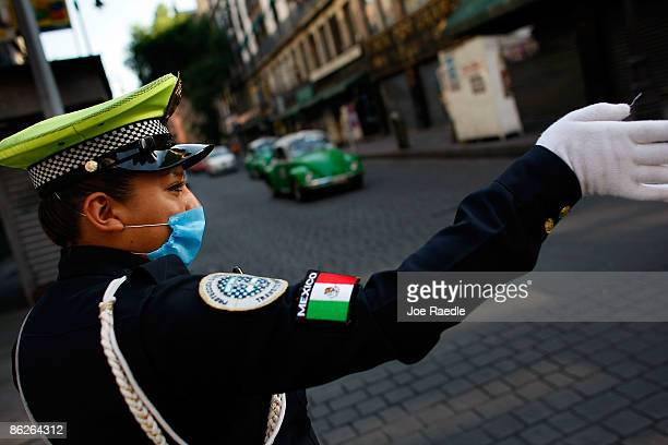A traffic patrol officer wears a surgical mask to help prevent being infected with the swine flu as she directs traffic on April 28 2009 in Mexico...