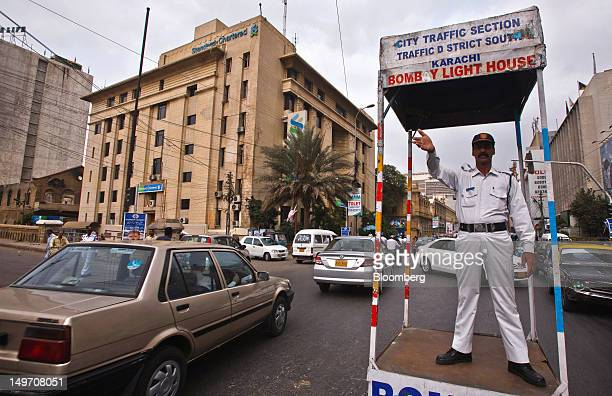 A traffic police officer guides traffic in front of the Standard Chartered Plc head office in Karachi Pakistan on Thursday July 26 2012 Standard...
