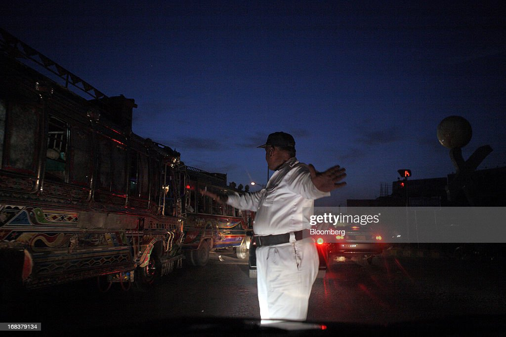 A traffic police officer stands and directs traffic through the streets of Karachi, Pakistan, on Wednesday, May 8, 2013. Pakistan is to hold parliamentary elections on May 11. According to opinion polls, Nawaz Sharif of the Pakistan Muslim League-N (PMLN) leads Imran Khan of Pakistan Tehrik-e-Insaf (PTI) in the race to replace president Asif Ali Zadari and become Pakistan's 12th president. Photographer: Asim Hafeez/Bloomberg via Getty Images