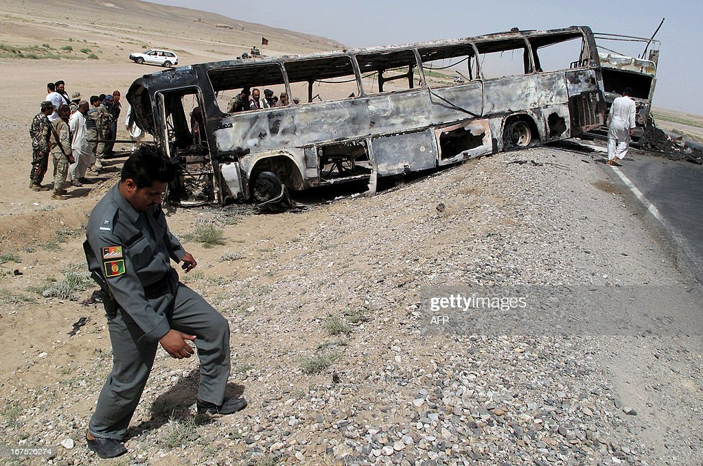 Traffic police officials inspect the site where a passenger bus collided with a fuel tanker truck in Kandahar province on April 26, 2013. A passenger bus in Afghanistan collided Friday with a wrecked fuel tanker left on a road after a Taliban insurgent attack, killing at least 45 people, officials said. AFP PHOTO/Noor MOHAMMAD