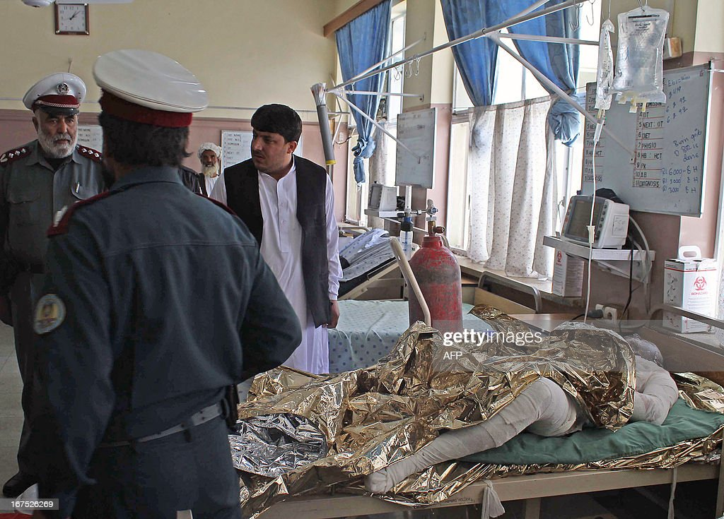 Traffic police officials visit a burn victim at a hospital following the collision of a passenger bus with a fuel tanker truck, at a hospital in Kandahar on April 26, 2013. A passenger bus in Afghanistan collided Friday with a wrecked fuel tanker left on a road after a Taliban insurgent attack, killing at least 45 people, officials said.