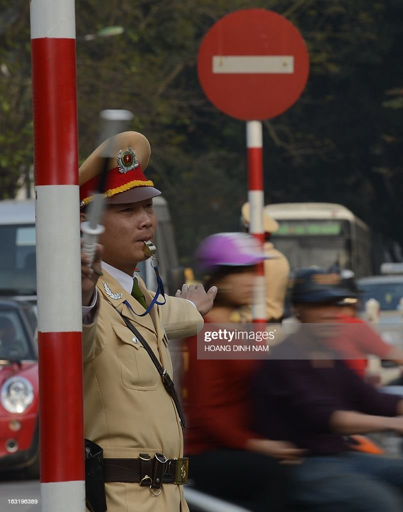 A traffic policeman directs traffic at an intersection in downtown Hanoi on March 6, 2013. Short, pot-bellied policemen will be banned from traffic duty in Vietnam's capital Hanoi and given office jobs in a bid to improve the force's public image, police said. AFP PHOTO/HOANG DINH Nam