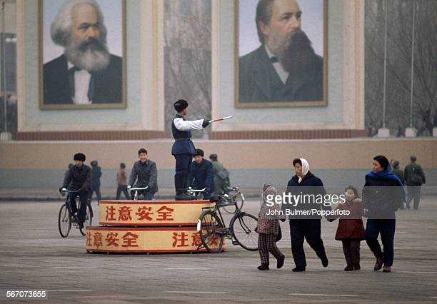 A traffic policeman in front of portraits of Karl Marx and Friedrich Engels in Beijing China during the Cultural Revolution 1973