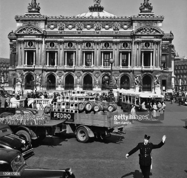 A traffic policeman on duty on the Place de l'Opera Paris circa 1949 Behind him is the Palais Garnier or Paris Opera