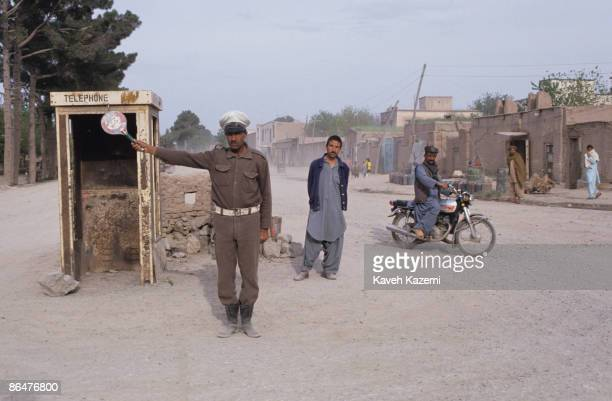 A traffic policeman stands next to an empty telephone booth directing the cars on a dusty main road in Herat in western Afghanistan 24th April 1992...