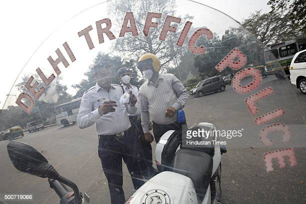 Traffic policemen wear antipollution masks to beat air pollution on December 9 2015 at Janpath Road in New Delhi In an attempt to tackle the...