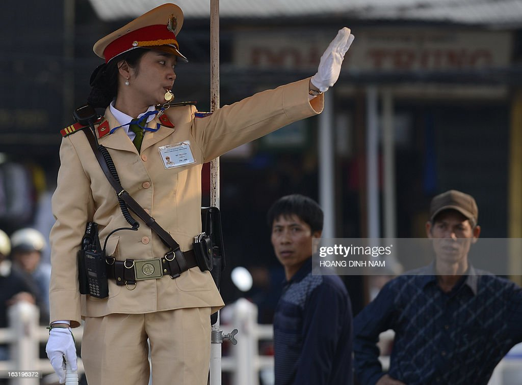 A traffic policewoman directs traffic at an intersection in downtown Hanoi on March 6, 2013. Short, pot-bellied policemen will be banned from traffic duty in Vietnam's capital Hanoi and given office jobs in a bid to improve the force's public image, police said. AFP PHOTO/HOANG DINH Nam