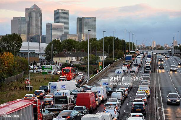 Traffic queues on a main route into London by the towers of London's financial district Canary Wharf on October 28 2013 after a strong storm causes...
