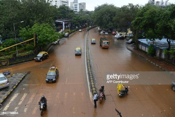 Traffic resumes on a muddy road after the water receded in Mumbai on August 30 following heavy rains that brought major flooding to the coastal city...