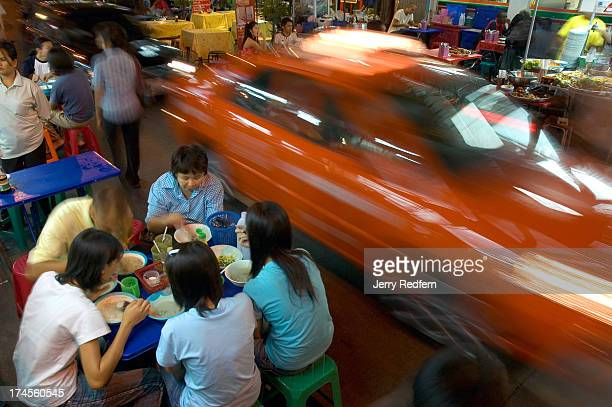 Traffic rolls by as a family tucks into dinner in a street food area in the Banglumpoo District