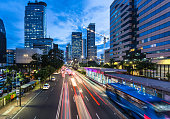 Traffic rushes in Jakarta business district along the city main avenue Jalan Thamrin at night in Indonesia capital city. The Transjakarta bus system enjoys its own traffic lane to avoid congestion.