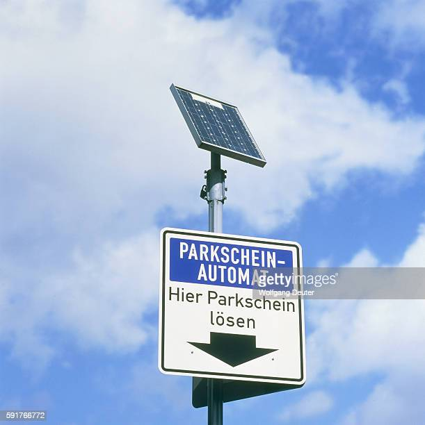Traffic sign parking ticket dispenser with solar cell against blue sky and white clouds, full sho